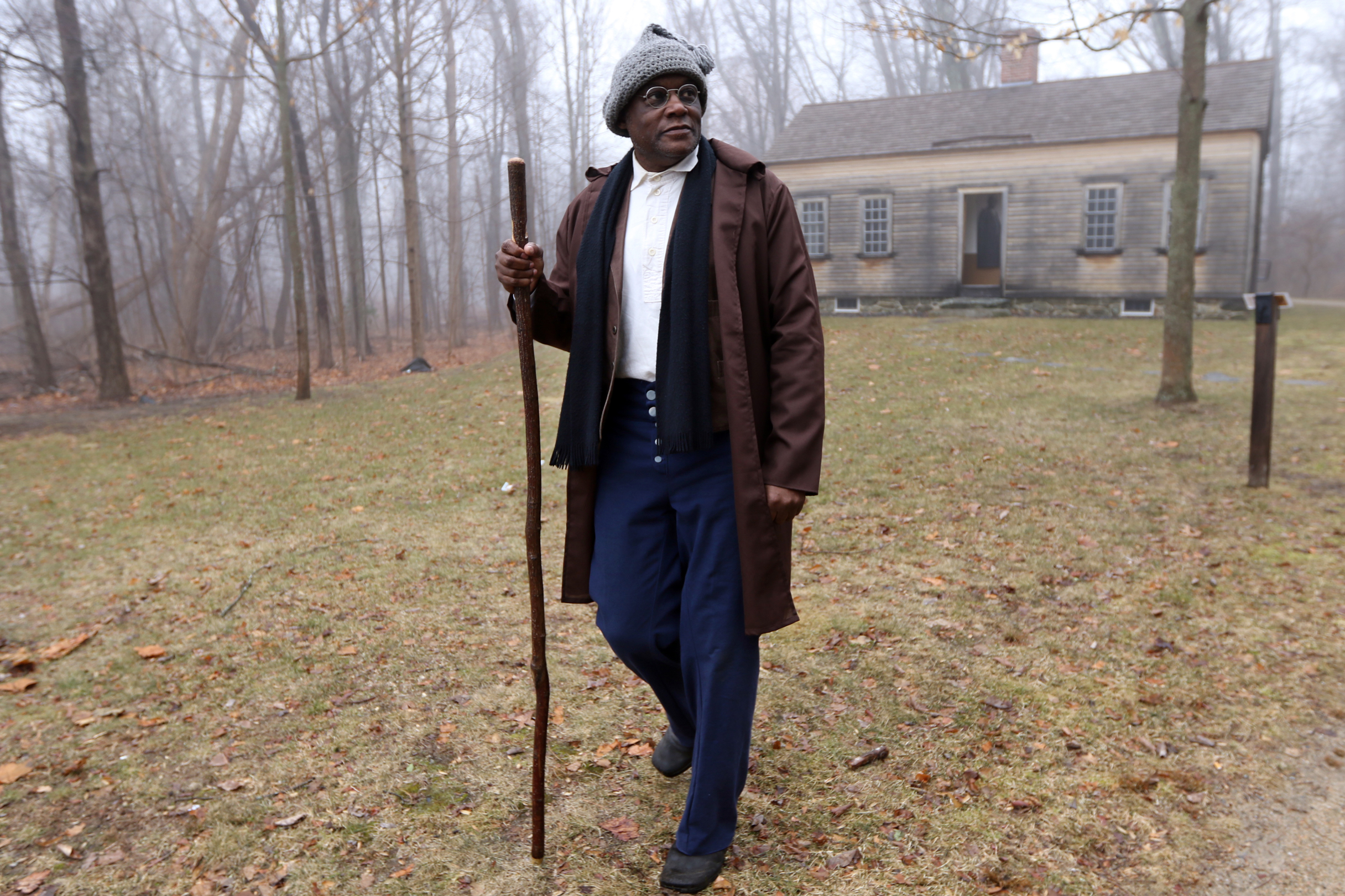 Joe Zellner, of Bedford, portraying Peter Robbins, walks out from the Robbins House in Concord to greet his audience Friday, Feb. 16, 2018. Students from Greenfield Commonwealth Virtual School went to the house to learn about the families who lived there and Concord's African American history. [Wicked Local Staff Photo/Ann Ringwood]